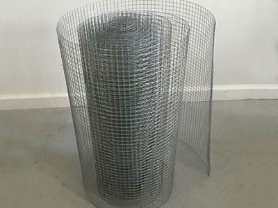 One galvanized wire mesh roll stands on the floor.